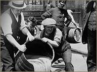 photo ancienne hommes manipulant un fut de rhum